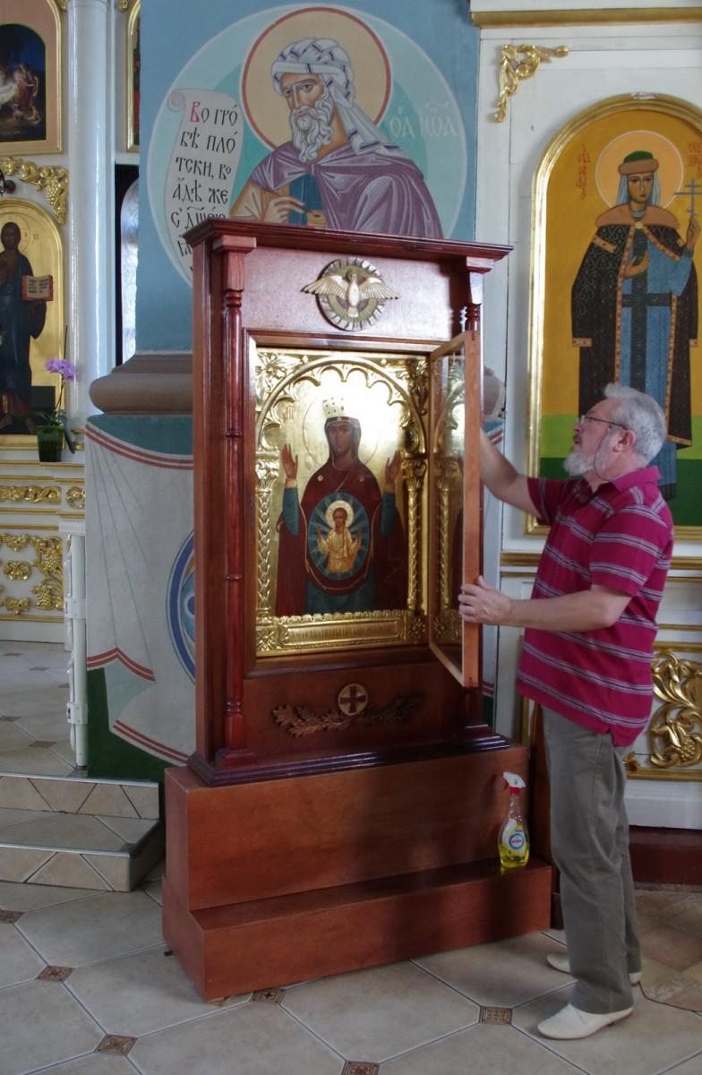 Павел Жаров устанавливает  воссозданную Логойскую икону в киот